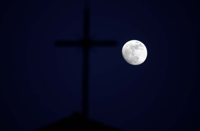 The 'super moon' full moon is seen in front of the cross of a church in Siero, Spain, January 29, 2018. REUTERS/Eloy Alonso