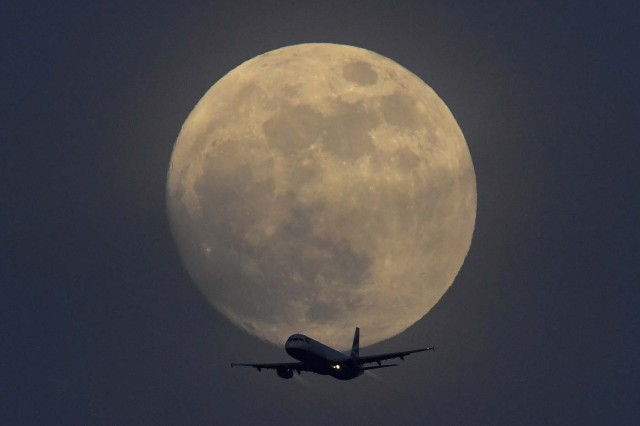 A British Airways aicraft flies infront of a full moon over London, Britain, January 30, 2018. REUTERS/Toby Melville