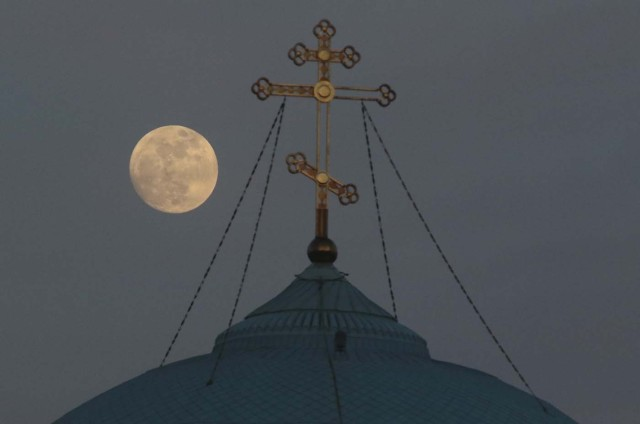 A supermoon rises behind the cross of the Saint Nicholas cathedral in the Black Sea port of Yevpatoriya, Crimea January 30, 2018. REUTERS/Pavel Rebrov