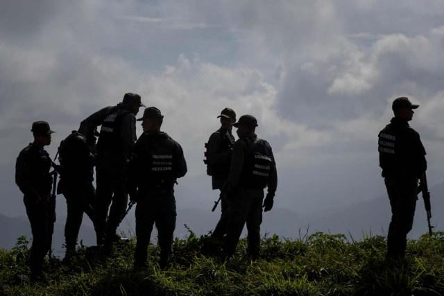 """CAR03. CARACAS (VENEZUELA), 15/01/2018.- Agentes prestan guardia en los alrededores del lugar donde se realiza una operación contra el grupo liderado por el policía Óscar Pérez hoy, lunes 15 de enero de 2018, en el barrio El Junquito, en Caracas (Venezuela). Las autoridades venezolanas desarticularon hoy el grupo liderado por el policía Oscar Pérez, acusado de """"ataque terrorista"""" al Supremo, e informaron de haber """"abatido"""" a un grupo no identificado de sus miembros y detenido a cinco. EFE/Miguel Gutiérrez"""