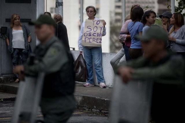 """CAR14. CARACAS (VENEZUELA), 17/01/2018.- Una mujer sostiene un cartel en el que se lee """"Yo soy Óscar Pérez"""" frente a miembros de la Guardia Nacional Bolivariana y la Policía Nacional Bolivariana que custodian las inmediaciones de la morgue en donde está cuerpo del exagente Pérez hoy, miércoles 17 de enero de 2018, en Caracas (Venezuela). Decenas de agentes de la Policía Nacional Bolivariana custodian desde la mañana de hoy los alrededores de la principal morgue de Caracas, después de que familiares de Óscar Pérez, el exagente alzado contra el Gobierno chavista quien falleció el lunes, exigieran identificar su cuerpo. EFE/MIGUEL GUTIÉRREZ"""
