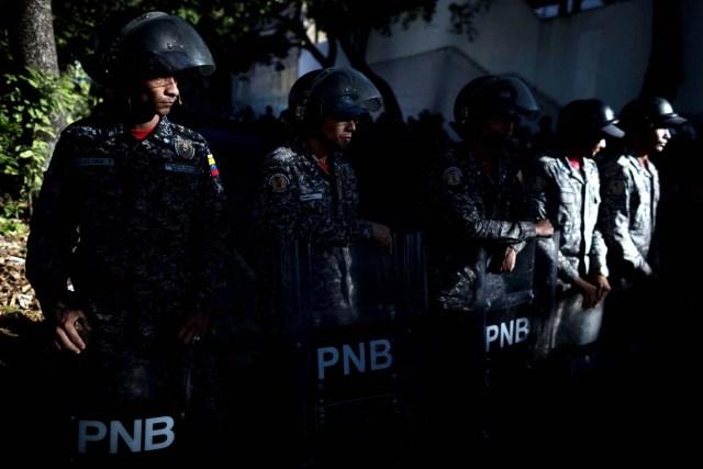 Miembros de la Policía Nacional Bolivariana (PNB) custodian las inmediaciones de la morgue mientras personas protestan en apoyo a los familiares de Oscar Pérez hoy, sábado 20 de enero del 2018, en Caracas (Venezuela). EFE/Miguel Gutiérrez