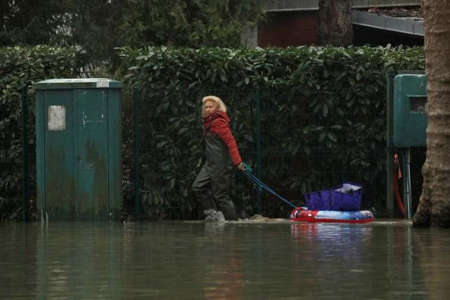 VAL107. VILLENNES SUR SEINE (FRANCIA), 30/01/2018.- Una mujer camina por una calle durante las inundaciones del río Sena a su paso por Villennes Sur Seine (Francia) hoy, 30 de enero de 2018. Las numerosas lluvias han provocado la crecida del Sena hasta causar inundaciones en París y sus alrededores. EFE/ Yoan Valat
