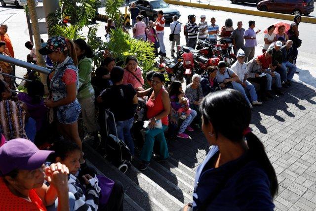 La gente espera en fila para comprar comida, en una acera frente a un supermercado en Caracas, Venezuela, el 6 de enero de 2018. REUTERS / Marco Bello