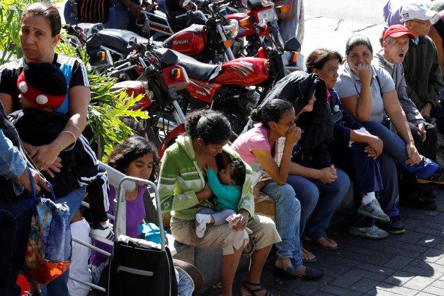 Una mujer amamanta a un niño mientras espera en una cola para comprar comida, en una acera frente a un supermercado en Caracas, Venezuela, el 6 de enero de 2018. REUTERS / Marco Bello