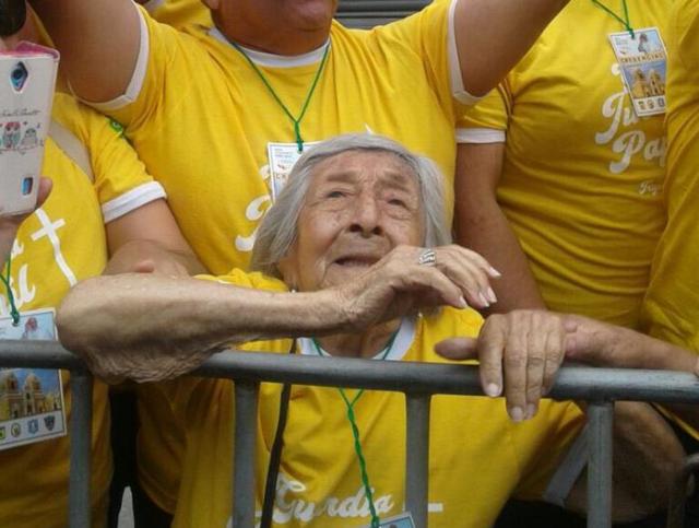 """Fotografía cedida por Vatican Media de un hombre sosteniendo un cartel en nombre de la señora Trinidad (frente) durante el paso del papa Francisco hoy, sábado 20 de enero de 2018, a Trujillo (Perú). El papa bajó hoy del papamóvil en uno de los trayectos por las calles de Trujillo, en Perú, para saludar a Trinidad, una mujer que llevaba un cártel que decía que cumplía 99 años y que estaba ciega y que quería tocar su mano. """"Me llamo Trinidad cumplo 99 años. No veo. Quiero tocar tu manito"""", se leía en el cártel que una persona levantaba con el deseo de la anciana en espera de que lo viese el papa a su paso por las calles de Trujillo. EFE/GREG BURKE/VATICAN MEDIA / SOLO USO EDITORIAL/NO VENTAS MEJOR CALIDAD DISPONIBLE"""