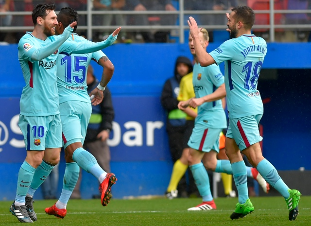 Barcelona's Argentinian forward Lionel Messi (L) and Spanish defender Jordi Alba (R) celebrate their team's opening goal during the Spanish league football match between SD Eibar and FC Barcelona at the Ipurua stadium in Eibar on February 17, 2018. / AFP PHOTO / ANDER GILLENEA