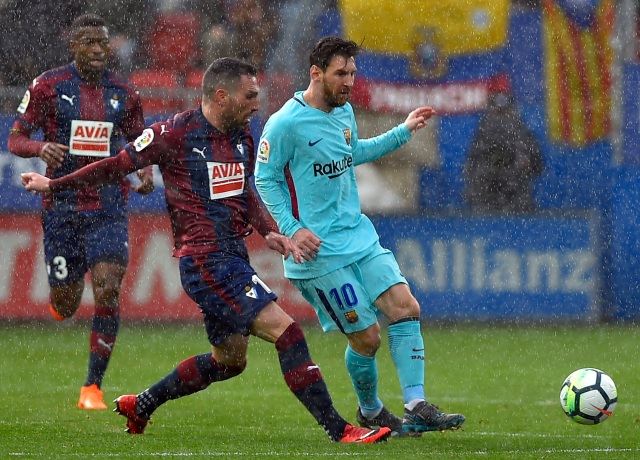 Barcelona's Argentinian forward Lionel Messi (R) vies with Eibar's Spanish defender Anaitz Arbilla during the Spanish league football match between SD Eibar and FC Barcelona at the Ipurua stadium in Eibar on February 17, 2018. / AFP PHOTO / ANDER GILLENEA