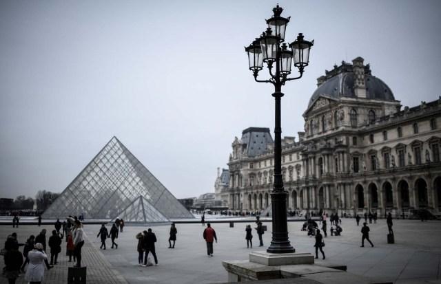 People walk towards the the Louvre Pyramid in Paris on February 19, 2018. / AFP PHOTO / STEPHANE DE SAKUTIN