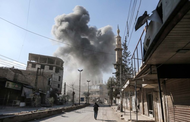 A picture taken on February 21, 2018 shows a smoke plume rising following a reported regime air strike in the rebel-held enclave of Hamouria in the Eastern Ghouta near Damascus. / AFP PHOTO / ABDULMONAM EASSA