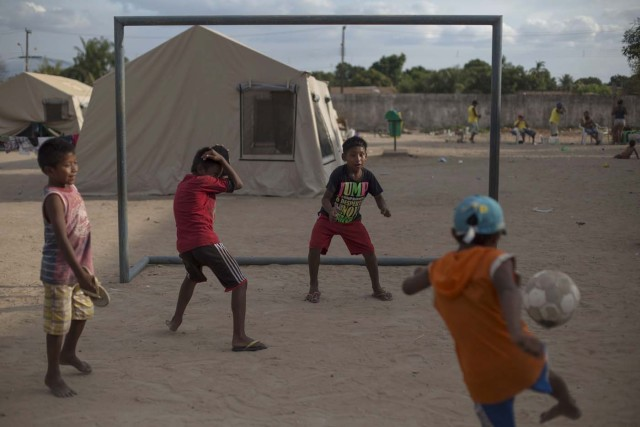 Children from the Venezuelan indigenous tribe Warao play football at a shelter in the city of Boa Vista, Roraima, Brazil, on February 24, 2018. According with local authorities, around one thousand refugees are crossing the Brazilian border each day from Venezuela. With the constant influx of Venezuelan immigrants most are living in shelters and the streets of Boa Vista and Paracaima cities. / AFP PHOTO / MAURO PIMENTEL