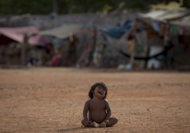 A Venezuelan indigenous refugee child cries at a shelter in the city of Boa Vista, Roraima, Brazil, on February 24, 2018. According with local authorities, around one thousand refugees are crossing the Brazilian border each day from Venezuela. With the constant influx of Venezuelan immigrants most are living in shelters and the streets of Boa Vista and Paracaima cities, looking for work, medical care and food. Most are legalizing their status to stay and live in Brazil. / AFP PHOTO / MAURO PIMENTEL