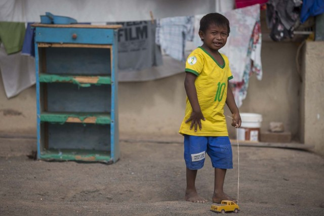 Venezuelan refugee child from Warao indigenous tribe plays with a toy inside a shelter in the city of Boa Vista, Roraima, Brazil, on February 24, 2018. According with local authorities, around one thousand refugees are crossing the Brazilian border each day from Venezuela. With the constant influx of Venezuelan immigrants most are living in shelters and the streets of Boa Vista and Paracaima cities, looking for work, medical care and food. Most are legalizing their status to stay and live in Brazil. / AFP PHOTO / MAURO PIMENTEL