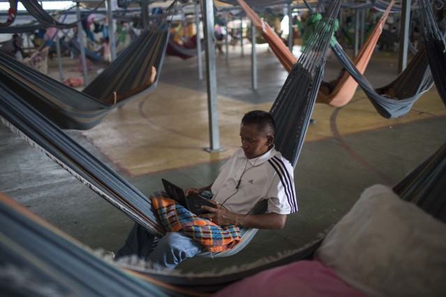 Venezuelan refugee indigenous watches a movie inside a shelter in the city of Boa Vista, Roraima, Brazil, on February 24, 2018. According with local authorities, around one thousand refugees are crossing the Brazilian border each day from Venezuela. With the constant influx of Venezuelan immigrants most are living in shelters and the streets of Boa Vista and Paracaima cities, looking for work, medical care and food. Most are legalizing their status to stay and live in Brazil. / AFP PHOTO / MAURO PIMENTEL