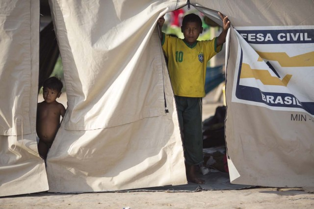A Venezuelan indigenous refugee child and youth look from a tent inside a shelter in the city of Boa Vista, Roraima, Brazil, on February 24, 2018. According with local authorities, around one thousand refugees are crossing the Brazilian border each day from Venezuela. With the constant influx of Venezuelan immigrants most are living in shelters and the streets of Boa Vista and Paracaima cities, looking for work, medical care and food. Most are legalizing their status to stay and live in Brazil. / AFP PHOTO / MAURO PIMENTEL