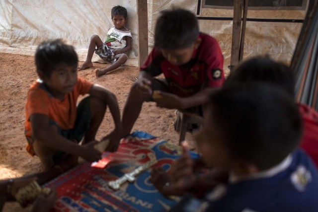 Venezuelan indigenous refugee children play dominos inside a shelter in the city of Boa Vista, Roraima, Brazil, on February 24, 2018. According with local authorities, around one thousand refugees are crossing the Brazilian border each day from Venezuela. With the constant influx of Venezuelan immigrants most are living in shelters and the streets of Boa Vista and Paracaima cities, looking for work, medical care and food. Most are legalizing their status to stay and live in Brazil. / AFP PHOTO / MAURO PIMENTEL