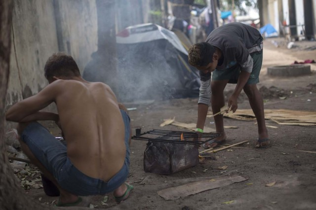 Venezuelan refugees cook inside a shelter in the city of Boa Vista, Roraima, Brazil, on February 24, 2018. According with local authorities, around one thousand refugees are crossing the Brazilian border each day from Venezuela. With the constant influx of Venezuelan immigrants most are living in shelters and the streets of Boa Vista and Paracaima cities, looking for work, medical care and food. Most are legalizing their status to stay and live in Brazil. / AFP PHOTO / MAURO PIMENTEL
