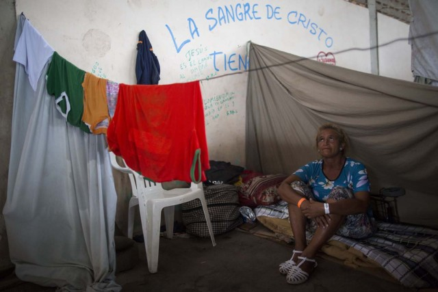 Maria Flores, 50, who works as housekeeper to send money to her family in Venezuela, sits inside a shelter in the city of Boa Vista, Roraima, Brazil, on February 24, 2018. According with local authorities, around one thousand refugees are crossing the Brazilian border each day from Venezuela. With the constant influx of Venezuelan immigrants most are living in shelters and the streets of Boa Vista and Paracaima cities, looking for work, medical care and food. Most are legalizing their status to stay and live in Brazil. / AFP PHOTO / MAURO PIMENTEL