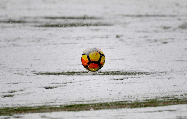 This photo taken on February 25, 2018 shows snow covering a ball and the pitch prior to the postponement of the Italian Serie A football match Juventus versus Atalanta at the Allianz Stadium in Turin.  The Italian Serie A football match Juventus versus Atalanta on February 25 has been postponed due to weather.  / AFP PHOTO / ALBERTO PIZZOLI