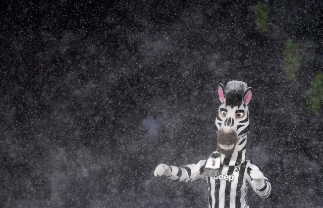 """Juventus mascot """"Jay"""" performs under heavy snowfall before the postponed Italian Serie A football match Juventus versus Atalanta on February 25, 2018 at the Allianz Stadium in Turin. The Italian Serie A football match Juventus versus Atalanta on February 25 has been postponed due to weather. / AFP PHOTO / ALBERTO PIZZOLI"""