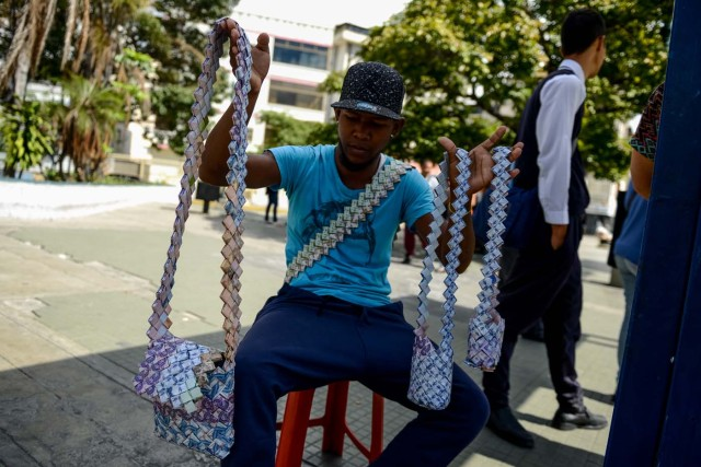 Wilmer Rojas, 25, shows the purses he sewn up, using Bolivar bills in Caracas, on January 30, 2018. A young Venezuelan tries to make a living out of devalued Bolivar banknotes by making crafts with them. / AFP PHOTO / FEDERICO PARRA