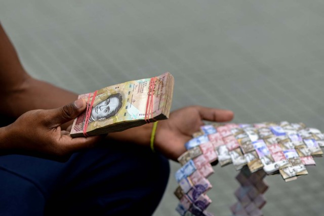 Wilmer Rojas, 25, holds a wad of Bolivar bills, which he uses to make crafts in Caracas on January 30, 2018. A young Venezuelan tries to make a living out of devalued Bolivar banknotes by making crafts with them. / AFP PHOTO / FEDERICO PARRA