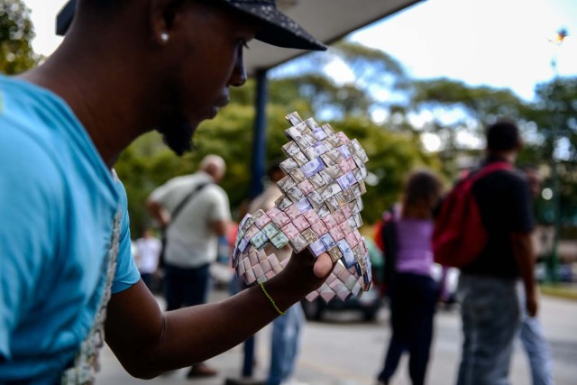 Wilmer Rojas, 25, shows a paper crown he sewn up, using Bolivar bills in Caracas, on January 30, 2018. A young Venezuelan tries to make a living out of devalued Bolivar banknotes by making crafts with them.  / AFP PHOTO / FEDERICO PARRA