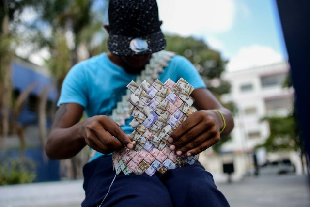 Wilmer Rojas, 25, sists at a bus stop in Caracas as he sews Bolivar bills, to make a paper crown on January 30, 2018. A young Venezuelan tries to make a living out of devalued Bolivar banknotes by making crafts with them. / AFP PHOTO / FEDERICO PARRA