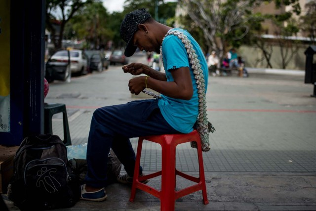 Wilmer Rojas, 25, sists at a bus stop in Caracas as he sews Bolivar bills, to make crafts on January 30, 2018. A young Venezuelan tries to make a living out of devalued Bolivar banknotes by making crafts with them. / AFP PHOTO / FEDERICO PARRA