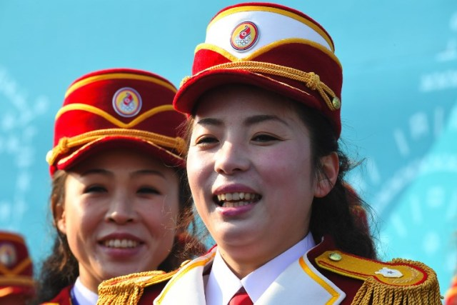 North Korean cheerleaders smile as they prepare to perform before a welcoming ceremony for North Korea's Olympic team at the Olympic Village in Gangneung on February 8, 2018 ahead of the Pyeongchang 2018 Winter Olympic Games. / AFP PHOTO / JUNG Yeon-Je