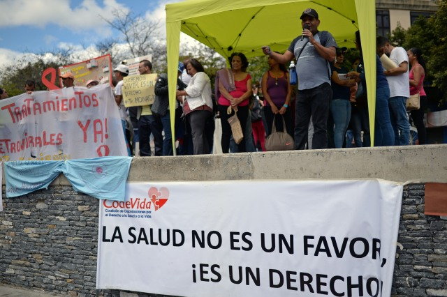 Kidney transplant patient Larry Zambrano (R), speaks during an anti-government demonstration against the shortage of medicines in Caracas on February 8, 2018. Zambrano is one of the 3,500 Venezuelan transplant patients, who are not receiveing the immunosuppressants necessary treatment, due to the shortage of medicines in the country. / AFP PHOTO / FEDERICO PARRA / TO GO WITH AFP STORY by Margioni BERMÚDEZ