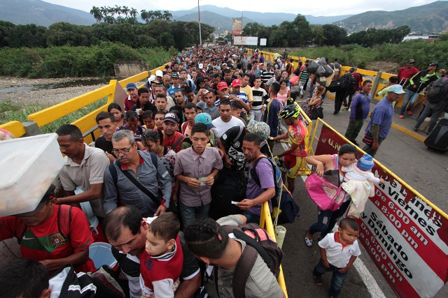 Venezuelan citizens cross the Simon Bolivar international bridge from San Antonio del Tachira in Venezuela to Norte de Santander province of Colombia on February 10, 2018. Oil-rich and once one of the wealthiest countries in Latin America, Venezuela now faces economic collapse and widespread popular protest. / AFP PHOTO / GEORGE CASTELLANOS