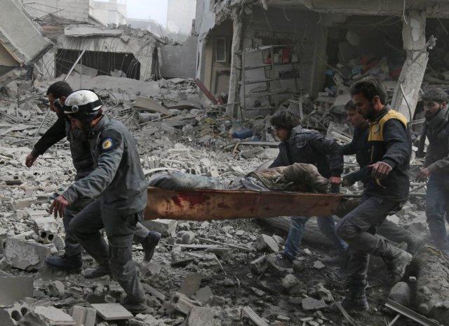 Evacuación de un herido tras un bombardeo en Saqba, al este de Guta (Siria), el 20 de febrero de 2018. Entre cerco y combates, la deterioración de la situación humanitaria ha alcanzado un punto drástico para los residentes de Guta Oriental, donde la muerte les acecha en forma de cazas que sobrevuelan sus cabezas y de la hambruna que les amenaza. (Foto: ABDULMONAM EASSA / AFP)