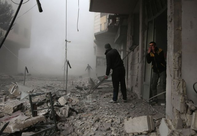 Al menos 15.000 vecinos han sido de nuevo desplazados de sus hogares huyendo de la artillería siria que este lunes han lanzado 260 morteros en el intervalo de dos horas, según el recuento que hace el Observatorio Sirio de Derechos Humanos. En la imagen, dos personas buscan víctimas entre los escombros en Hamouria, en Guta oriental, el 20 de febrero de 2018. (Foto: ABDULMONAM EASSA / AFP)