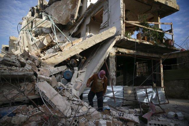 """Por primera vez en 80 días, un convoy humanitario conjunto entre la ONU y la Media Luna Roja Siria logró traspasar el cerco la semana pasada. """"Las familias allí asediadas solo pueden permitirse una comida diaria y los casos de malnutrición infantil se han disparado"""", reza un comunicado de la ONU. En la imagen, una persona entre los escombros de un edificio dañado por los bombardeos en Duma (Siria), el 20 de febrero de 2018. (Foto: BASSAM KHABIEH / REUTERS)"""
