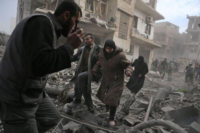Un grupo de personas huye de los bombardeos en Saqba, en la región de Guta oriental en Siria, el 20 de febrero de 2018. La ONU contabiliza en 393.000 los habitantes de Guta Oriental, al este de Damasco, que desde 2013 malviven bajo un doble cerco impuesto por las tropas regulares sirias en el perímetro exterior y por las milicias islamistas que controlan el interior de las barriadas cercadas. (Foto: ABDULMONAM EASSA / AFP)