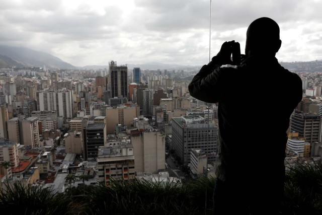 A man uses his phone to take a photo of Caracas as seen from the top of the Venezuela's Central Bank building in Caracas, Venezuela, January 31, 2018. REUTERS/Marco Bello