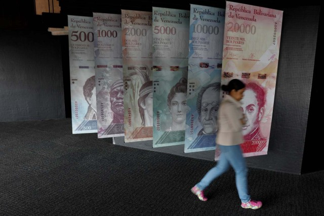 A woman walks by banners of Venezuelan bolivar notes displayed at the Venezuelan Central Bank building in Caracas, Venezuela, January 31, 2018. REUTERS/Marco Bello