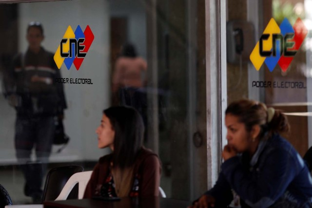 People walk past a logo of the National Electoral Council (CNE) at its headquarters in Caracas, Venezuela February 5, 2018. REUTERS/Marco Bello