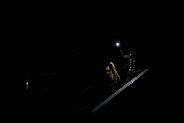 People use light from a phone while they walk on the staircase of a parking garage during a blackout in Caracas, Venezuela February 6, 2018. REUTERS/Carlos Garcia Rawlins