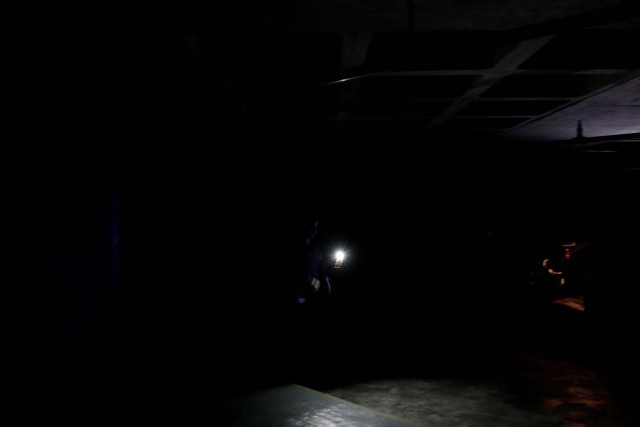 A woman uses light from a phone to find her car at a parking garage during a blackout in Caracas, Venezuela February 6, 2018. REUTERS/Carlos Garcia Rawlins