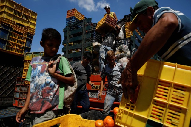 "A child looks at a basket filled with mandarins while workers load merchandise into Humberto Aguilar's truck at the wholesale market in Barquisimeto, Venezuela January 30, 2018. REUTERS/Carlos Garcia Rawlins TPX IMAGES OF THE DAY SEARCH ""LAWLESS ROADS"" FOR THIS STORY. SEARCH ""WIDER IMAGE"" FOR ALL STORIES.?"