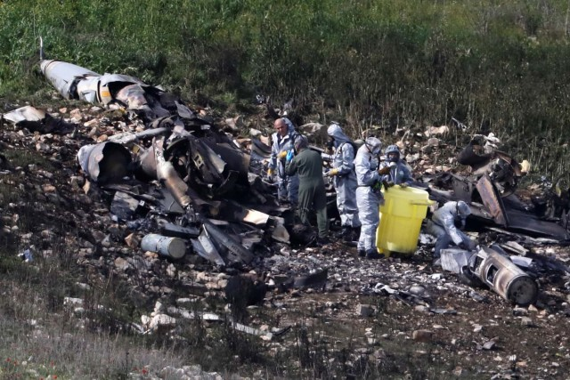 Israeli security forces examine the remains of an F-16 Israeli war plane near the village of Harduf, Israel February 10, 2018. REUTERS/Ronen Zvulun