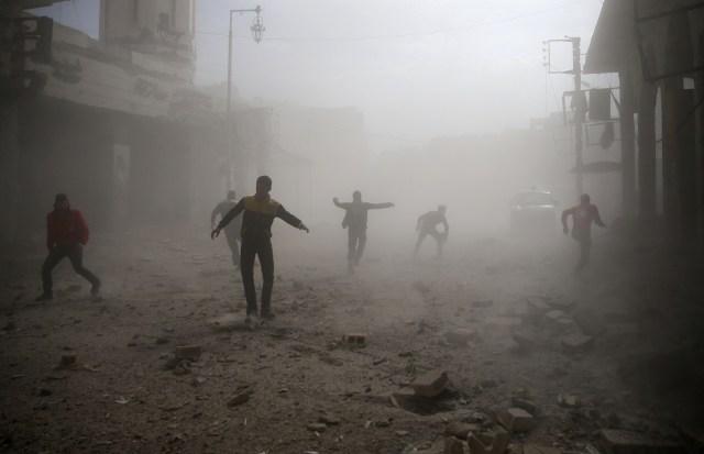 Civiles y miembros de la Defensa Civil huyendo de un ataque aéreo en Douma, Siria, feb 6, 2018. REUTERS/ Bassam Khabieh