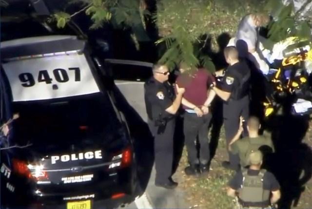 Un hombre esposado es conducido por la policía cerca de la escuela secundaria Marjory Stoneman Douglas luego de un tiroteo en Parkland, Florida, 14 de febrero de 2018 in a still image from video. WSVN.com via REUTERS