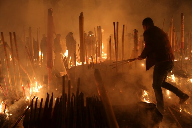 People burn incense sticks and pray for good fortune at Giant Buddhist Temple on the first day of the Chinese Lunar New Year of Dog, in Chongqing, China, February 16, 2018. Picture taken February 16, 2018. REUTERS/Stringer  ATTENTION EDITORS - THIS IMAGE WAS PROVIDED BY A THIRD PARTY. CHINA OUT.