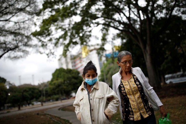 Yasmira Castano (L), 40, who lost her transplanted kidney, walks helped by her mother after she received a dialysis session at a state hospital in Caracas, Venezuela February 14, 2018. Castano was unable to find the drugs needed to keep her body from rejecting the organ. On Christmas Eve 2017, she was rushed to a state hospital. Her immune system had attacked the foreign organ and she lost her kidney shortly afterwards. Picture taken February 14, 2018. REUTERS/Carlos Garcia Rawlins