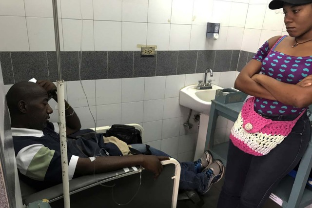 Pablo Tejada, a kidney transplanted patient, receives treatment in front of his daughter at a state hospital in Caracas, Venezuela February 7, 2018. Tejada has been unable to find the drugs needed to keep his body from rejecting the transplanted kidney and his immune system is attacking the foreign organ. Picture taken February 7, 2018. REUTERS/Carlos Garcia Rawlins
