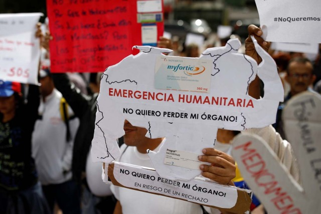 "Reinaldo Olivares, a kidney transplanted patient, holds a placard with the shape of the map of Venezuela that reads, ""Humanitarian emergency. I do not want to lose my organ"", during a protest against medicinal shortages in Caracas, Venezuela February 8, 2018. Picture taken February 8, 2018. REUTERS/Carlos Garcia Rawlins"