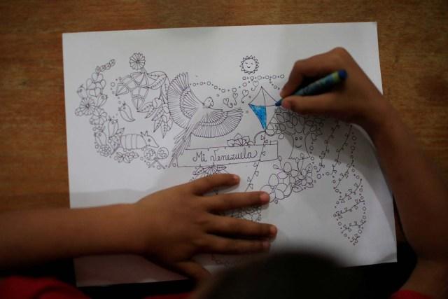 A child colors a graphic design in the shape of Venezuela in the slum of Petare in Caracas, Venezuela February 22, 2018. REUTERS/Marco Bello